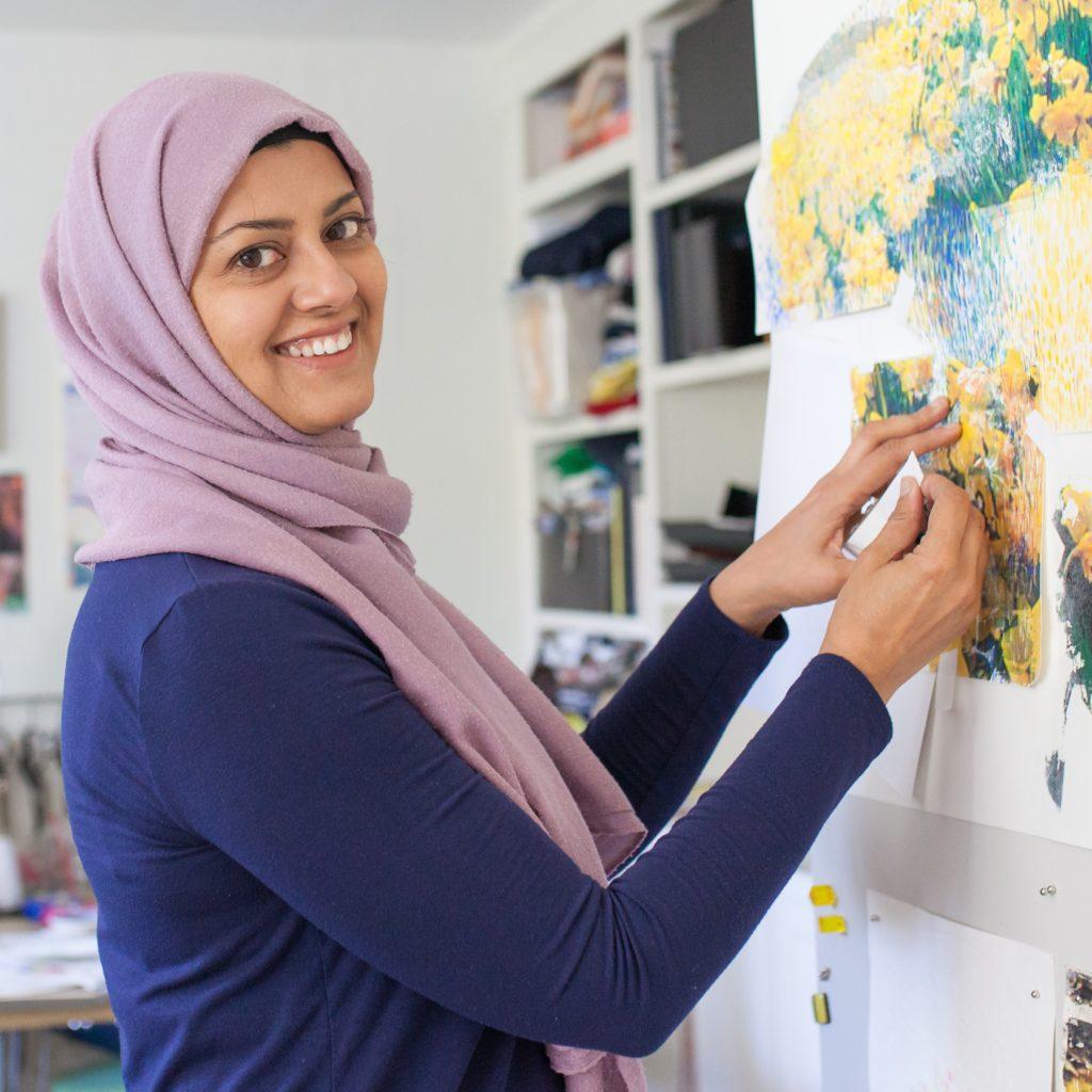 Artist Bushra Gill standing in front of her work